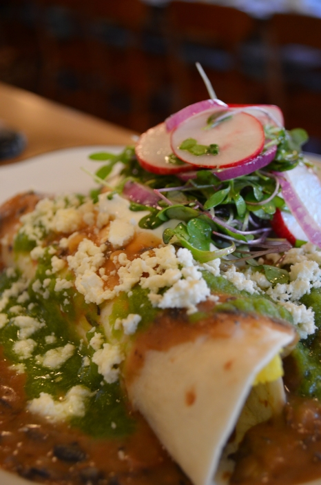 Two four tortila's filled with eggs and beans topped with salsa verde, black bean puree, sour cream, queso fresco, red onions, radishes and mixed micro green salad.